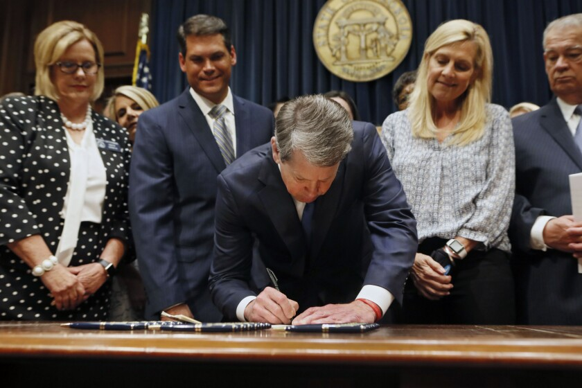 """FILE - Georgia's Republican Gov. Brian Kemp, center, signs legislation Tuesday, May 7, 2019, in Atlanta, banning abortions once a fetal heartbeat can be detected, which can be as early as six weeks before many women know they're pregnant. A federal judge is permanently blocking Georgia's 2019 """"heartbeat"""" abortion law, finding that it violates the U.S. Constitution. U.S. District Judge Steve Jones ruled against the state Monday, July 13, 2020, in a lawsuit filed by abortion providers and an advocacy group. (Bob Andres/Atlanta Journal-Constitution via AP, File)/Atlanta Journal-Constitution via AP)"""