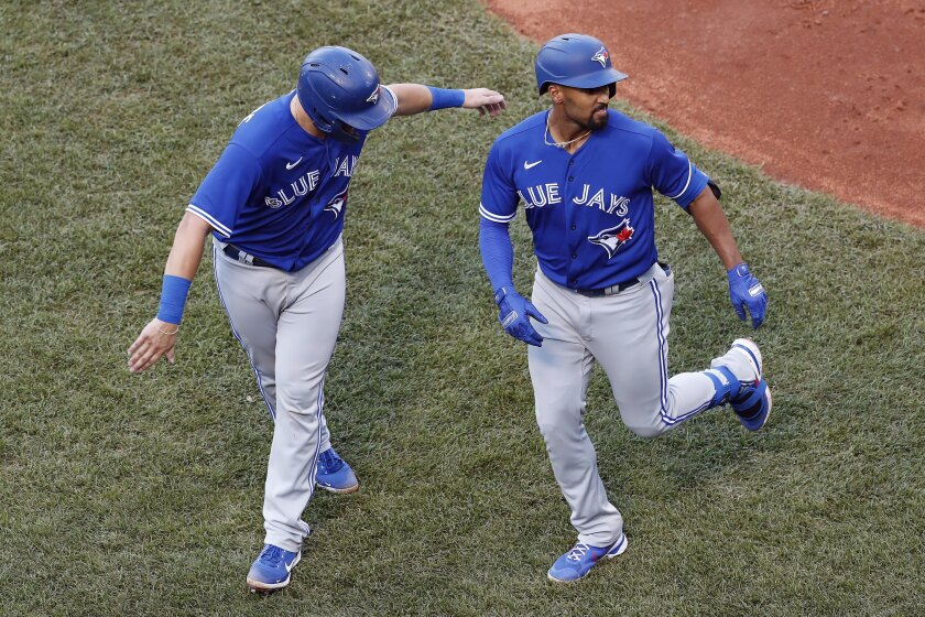 Toronto Blue Jays' Marcus Semien, right, celebrates his two-run home run that also drove in Reese McGuire, left, during the fifth inning of a baseball game against the Boston Red Sox, Saturday, June 12, 2021, in Boston. (AP Photo/Michael Dwyer)