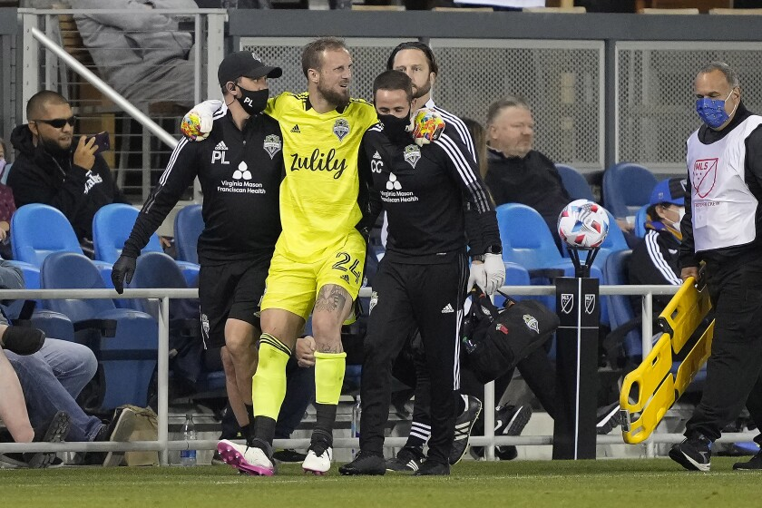Seattle Sounders goalkeeper Stefan Frei (24) is taken off the field after a collision with a San Jose Earthquakes player during the second half of an MLS soccer match Wednesday, May 12, 2021, in San Jose, Calif. The Sounders won 1-0. (AP Photo/Tony Avelar)