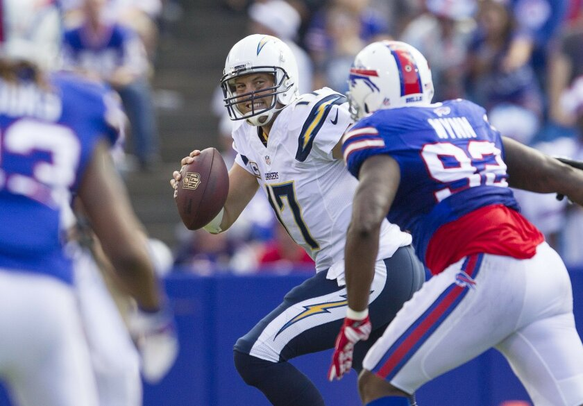The San Diego Chargers vs. The Buffalo Bills at Ralph Wilson Stadium.San Diego Chargers quarterback Philip Rivers (17) forced from the pocket by Buffalo Bills defensive end Jarius Wynn (92) in the third quarter.