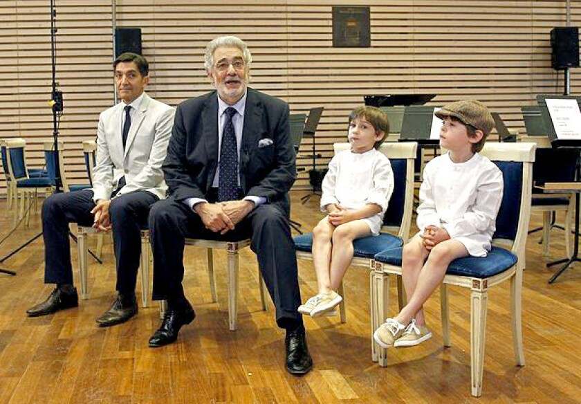 A day after being released from the hospital, Spanish tenor Placido Domingo speaks to journalists at Teatro Real in Madrid on Sunday. Appearing with him, from left, are his doctor Carlos Gonzalez and his grandsons Alvaro and Pablo.