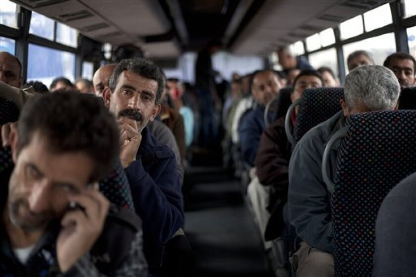 """Palestinians laborers ride a Palestinian-only bus on route to the West Bank from working in Tel Aviv area, Israel, Monday, March 4, 2013. Israel's decision to launch a pair of """"Palestinian-only"""" bus lines in the West Bank condemned by critics as racism and hailed by Israel as a goodwill gesture hav"""