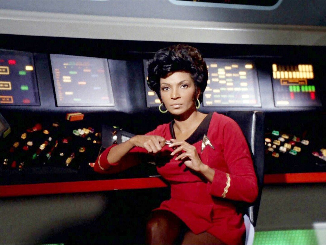 A woman in a red Star Trek dress at a control panel