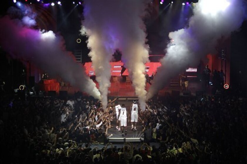 In this July 9, 2010, photo, Miami Heat basketball players Dwyane Wade (3), Chris Bosh (1) and LeBron James (6) leave the stage during a welcome celebration at American Airlines Arena in Miami. The Miami Dolphins have long dominated the affection of South Florida sports fans, but with the Heat's signing of the trio, the Dolphins suddenly find themselves fighting for attention. (AP Photo/Lynne Sladky)