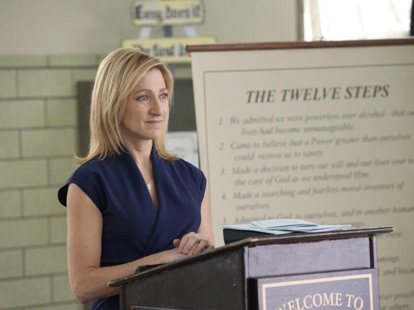 "Edie Falco at a lectern with ""The Twelve Steps"" behind her in ""Nurse Jackie."""
