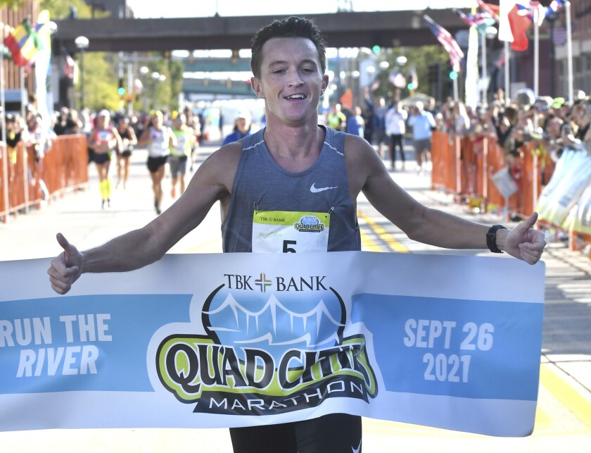 Tyler Pence of Springfield, Ill., finishes first in the TBK Bank Quad Cities Marathon on Sunday, Sept. 26, 2021, in Moline, Ill. An Illinois man unexpectedly won the Quad Cities Marathon this weekend when the two Kenyan runners who had far outpaced him were disqualified after being diverted off the course by a race volunteer bicyclist. Tyler Pence crossed the finish line in 2 hours, 15 minutes, 6 seconds to become the first U.S. runner since 2001 to win the race. (Gary L. Krambeck/Quad City Times via AP)
