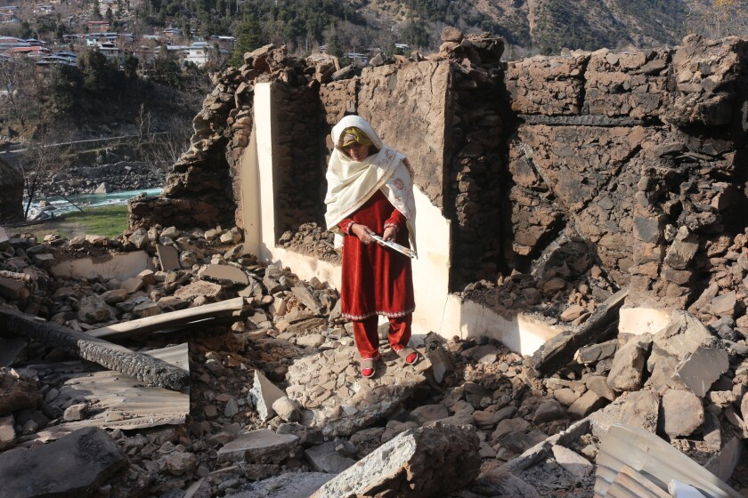 A Pakistani Kashmiri woman stands amid debris of her home that reportedly was destroyed by cross border shelling from Indian troops, in Neelum Valley, situated at the Line of Control in Pakistani Kashmir.