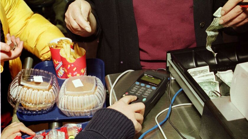 A student at Welsh Valley Middle School in Penn Valley, Pa., buys lunch using a machine that reads fingerprints in this 2001 file photo. The Vista Unified School District has been rolling out a program in which students' encrypted fingerprints are linked to their lunch accounts.