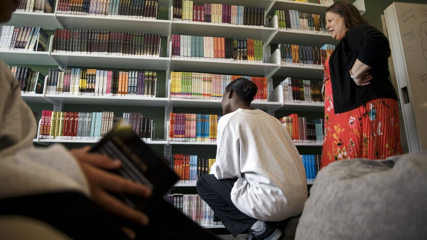 Amy Trulock, right, a full-time on-site librarian, watches as the girls browse the shelves inside the Los Padrinos Juvenile Hall library.