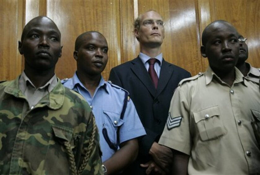 Thomas Cholmondeley, center, stands surrounded by police officers as a judge read the verdict finding him guilty of manslaughter, Thursday, May 7, 2009 in the Nairobi high court, Kenya. A court has convicted a descendant of Kenya's most famous white settlers of manslaughter in the shooting death of a black man on his vast estate, a case that has stirred simmering tensions over race and land in Kenya.Thomas Cholmondeley, 40, wearing a blue suit and red tie, looked down when the verdict was read; some of his family and friends started crying.(AP Photo/Karel Prinsloo)