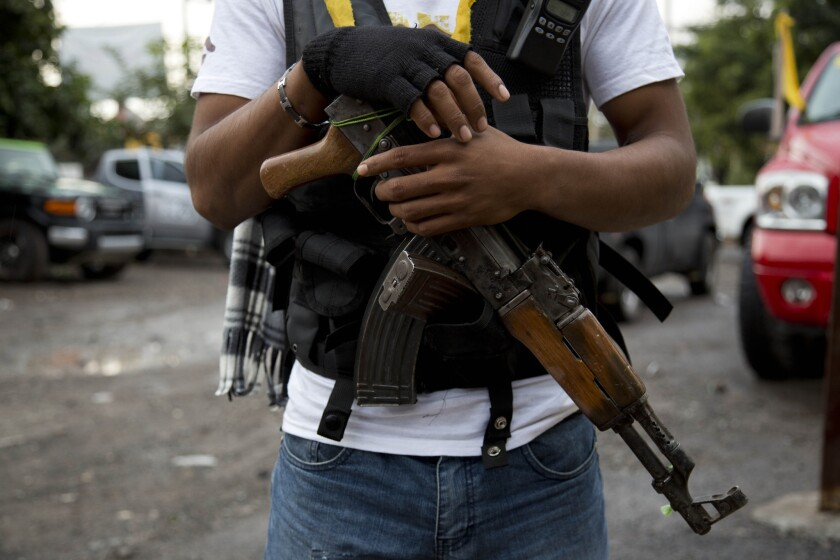 """A member of a """"self-defense"""" group in the Mexican state of Michoacan stands guard recently at a checkpoint at the entrance to the town of Antunez."""