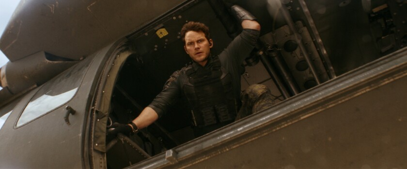 """Chris Pratt's character looks out the open door of a military helicopter in the movie """"The Tomorrow War."""""""