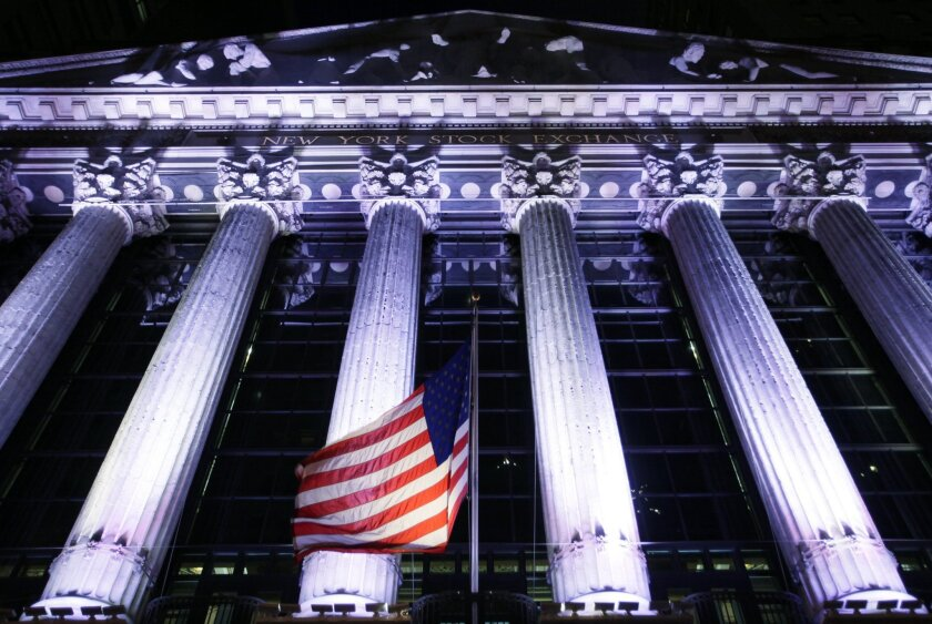 An American flag flies in front of the New York Stock Exchange, Wednesday, Oct. 8, 2014 in New York. Stocks are moving between gains and losses in early trading as traders digest the latest corporate earnings news. Later Wednesday the Federal Reserve releases minutes from its latest policy meeting last month. (AP Photo/Mark Lennihan)
