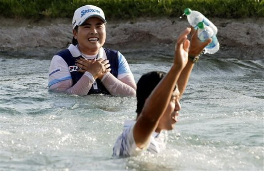 Inbee Park, left, of South Korea, celebrates after jumping into Poppy's Pond after winning the LPGA Kraft Nabisco Championship golf tournament in Rancho Mirage, Calif., Sunday, April 7, 2013. (AP Photo/Chris Carlson)
