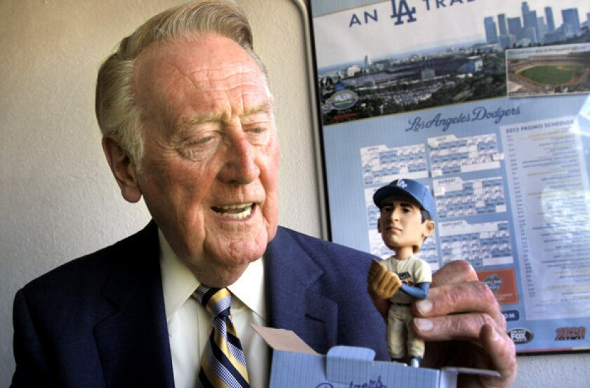 Vin Scully, taking a look at a Sandy Koufax bobblehead, was to have gotten a new bobblehead of himself this season.