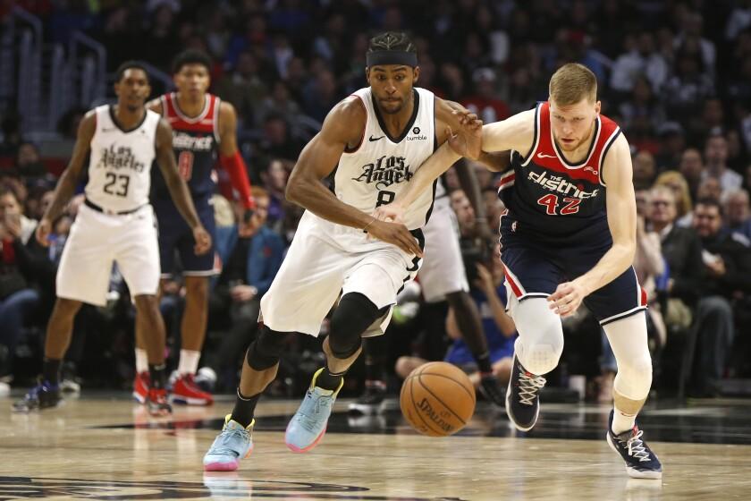 Clippers forward Maurice Harkless, left, battles Washington Wizards forward Davis Bertans for control of the ball.