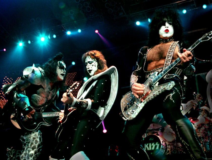 Three rock stars in heavy makeup and costumes perform onstage
