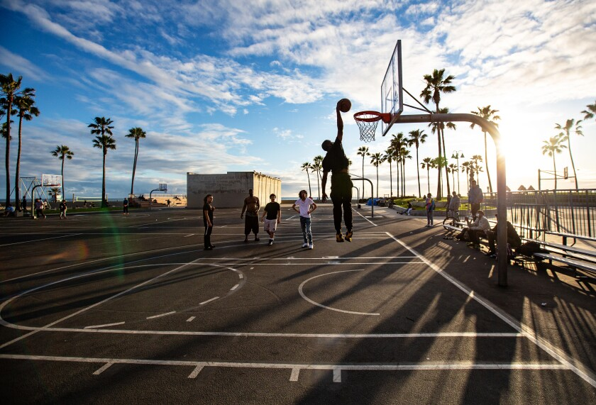 A man dunks on the basketball courts at Venice Beach on Thursday.