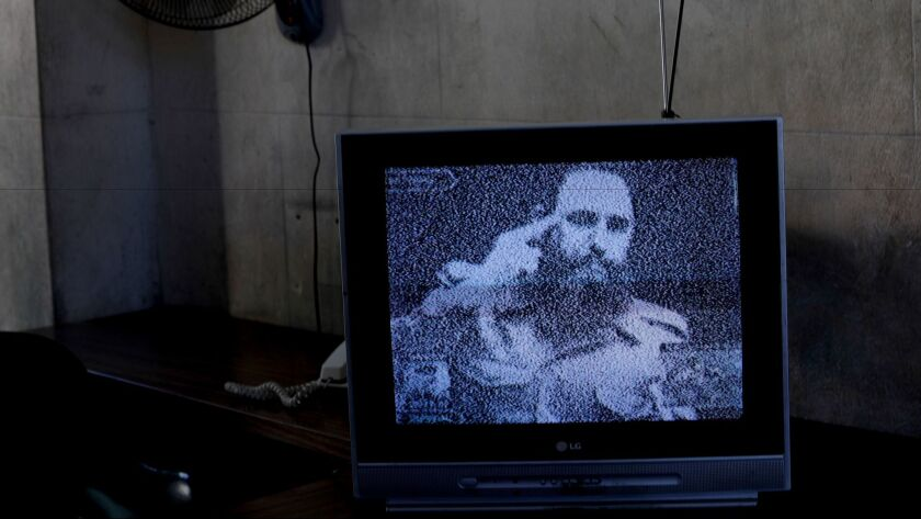 Footage of Fidel Castro plays on a television set outside of Havana after his death.
