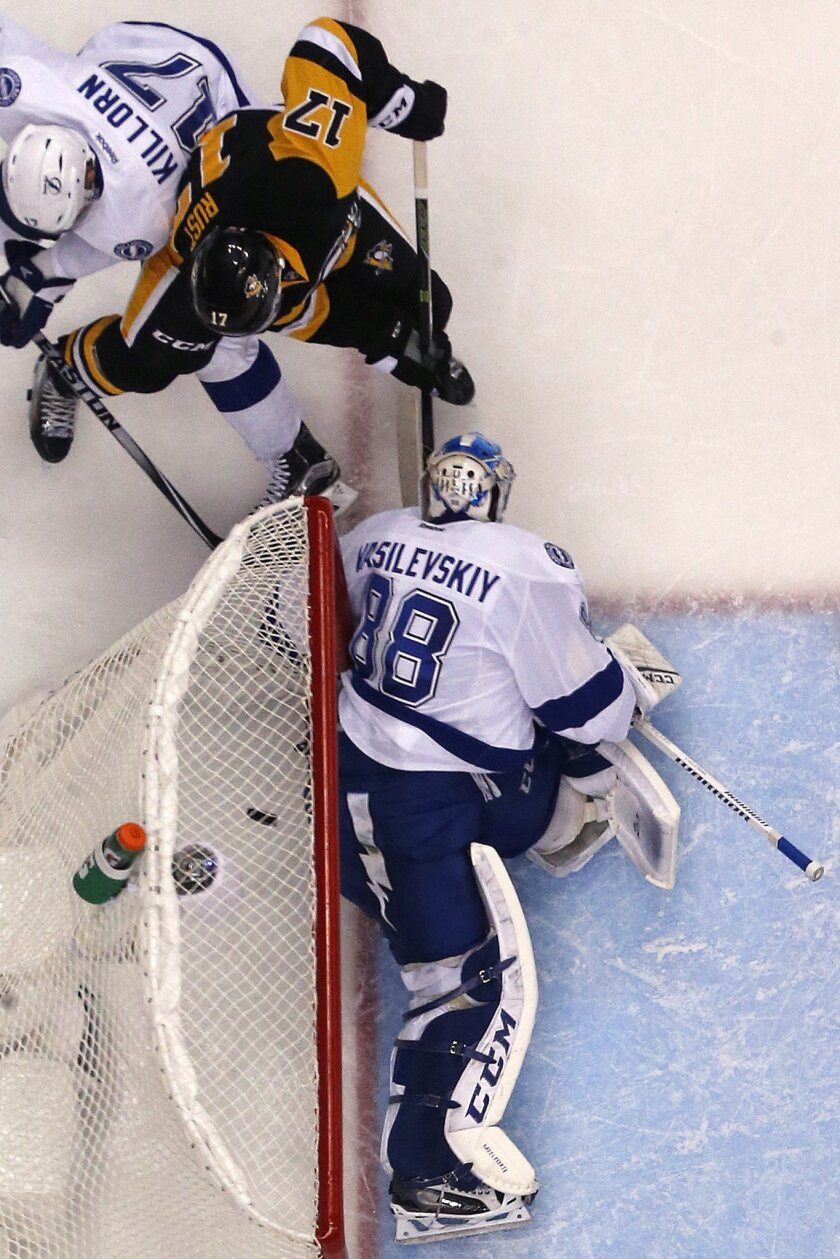 Pittsburgh Penguins' Bryan Rust (17) pokes the puck under the pad of Tampa Bay Lightning goalie Andrei Vasilevskiy (88) with Alex Killorn (17) defending for a goal during the second period of Game 7 of the NHL hockey Stanley Cup Eastern Conference finals Thursday, May 26, 2016, in Pittsburgh. The P