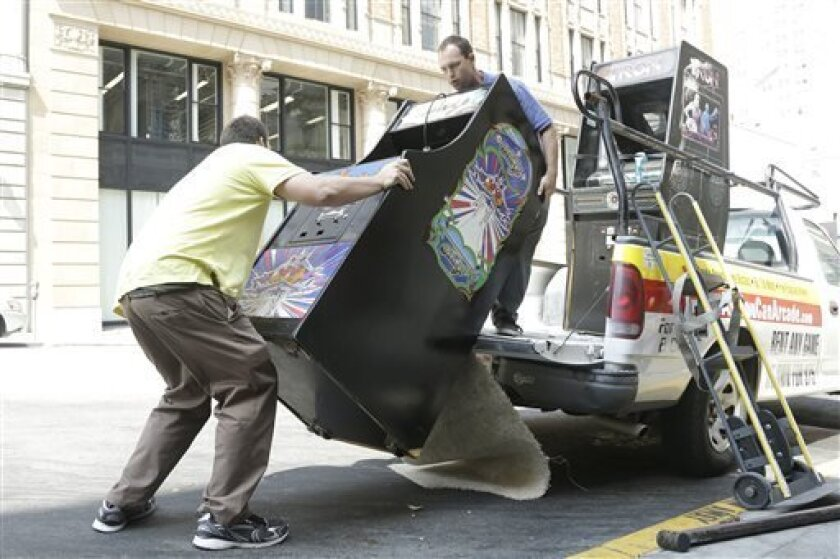 Timothy Peterson, left, and his brother Seth, co-owners of All You Can Arcade, unload a Galaga arcade game from their truck as they deliver it to the Eleven Inc office in San Francisco, Tuesday, July 30, 2013. A new startup company run by two San Francisco Bay area brothers will deliver any of a suite of retro 1980s classic video games and let you keep them in your home or office for $75 per month. (AP Photo/Jeff Chiu)