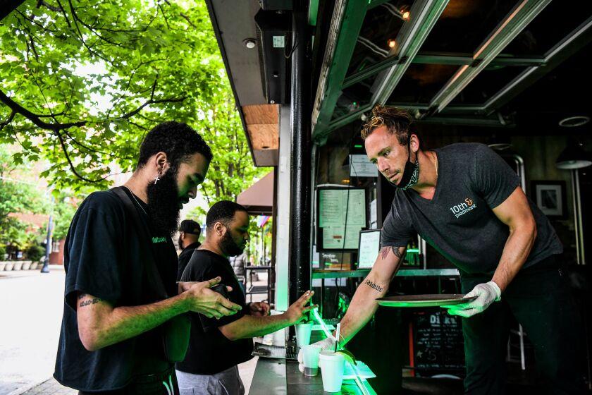 Bartender Jake Glazier serves customers at a reopened roadside bar in Atlanta