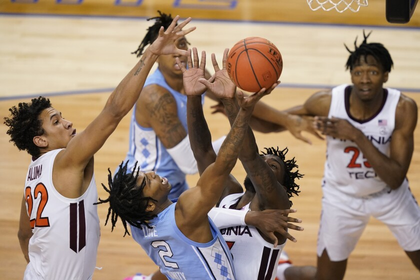 North Carolina guard Caleb Love (2) goes up for a shot as Virginia Tech forward Keve Aluma (22) and teammate guard Tyrece Radford, left, during the second half of an NCAA college basketball game in the quarterfinal round of the Atlantic Coast Conference tournament in Greensboro, N.C., Thursday, March 11, 2021. (AP Photo/Gerry Broome)