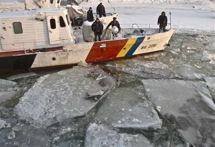 The crew of a border patrol ship waits as their boat is freed from frozen Danube waters by an ice breaker, in Giurgiu, southern Romania, Wednesday, Feb. 8, 2012. Bulgaria and Romania are suspending all shipping on the Danube River due to severe frost and the vast amount of ice blocking the heavily traveled waterway, Bulgaria's Transport Ministry said Wednesday.Authorities say up to 90 percent of the river surface is covered with floating ice, making it extremely difficult to traverse Europe's main commercial waterway, which winds 2,860-kilometer (1,777-mile) from Germany and serves as the natural border between Bulgaria and Romania.(AP Photo/Vadim Ghirda)