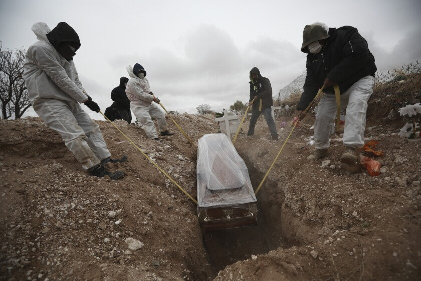 Four men lower a coffin into the ground.