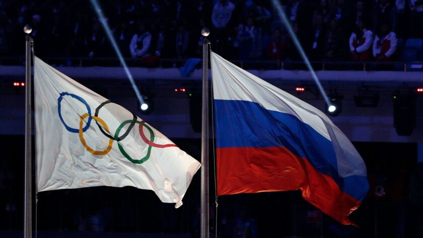 The Russian flag flies next to the Olympic flag during the closing ceremony of the Winter Olympics in Sochi, Russia, on Feb. 23, 2014.
