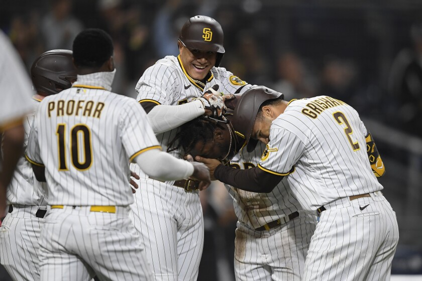 The Padres' Jorge Mateo is mobbed by teammates