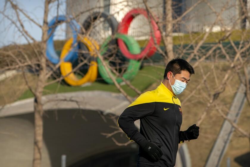 Un individuo con una mascarilla trota frente a los anillos olímpicos en Torre Olímpica de Beijing