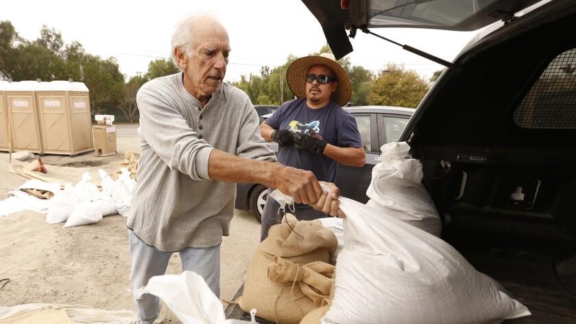 MALIBU, CA - NOVEMBER 19, 2018. Victor Lobl, loads sandbags provided by the LA County Fire Departmen