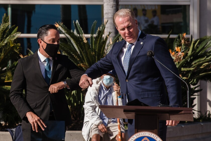 Mayor Kevin Faulconer, right, introduces Mayor-elect Todd Gloria in front of the San Diego Convention Center.