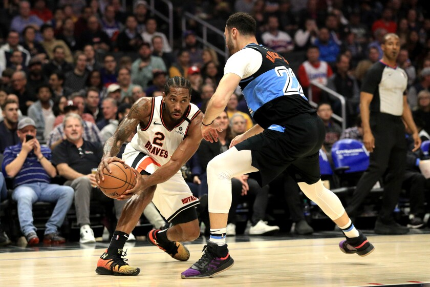 Cleveland Cavaliers' Larry Nance Jr. (22) defends against the dribble of Clippers' Kawhi Leonard (2) during the first half at Staples Center on Tuesday.