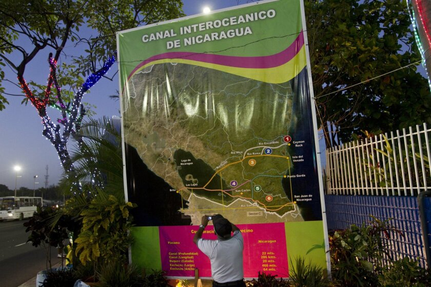 In this Dec. 4, 2013 photo, Oscar Torres, a 62-year-old retired construction worker takes photos of a banner showing a map of Nicaragua with possible routes of the Inter-Oceanic canal in Managua, Nicaragua. Six months after the Sandinista government granted a Chinese businessman a 100-year concessi