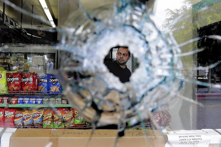 Michael Hassan, owner of I.V. Deli Mart in Isla Vista, is seen through a bullet hole in a store window. Elliot Rodger killed six people and injured 13 during a rampage in the college community May 23.