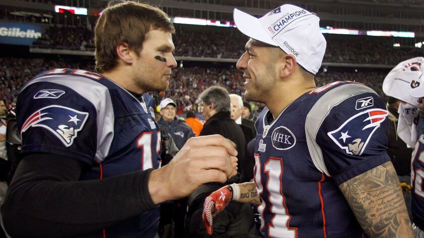 New England quarterback Tom Brady, left, congratulates Aaron Hernandez after the AFC championship ga