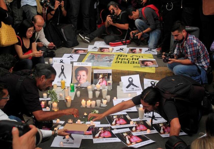 Periodistas colocan veladoras y fotografías de colegas asesinados en los últimos meses en México durante una protesta en Ciudad de México. EFE/Archivo