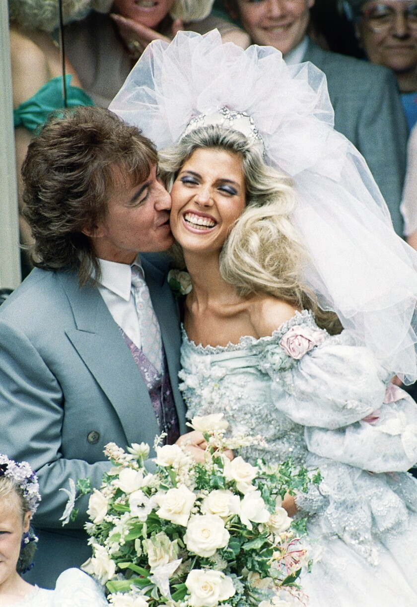 Rock star Bill Wyman (52) of The Rolling Stones pop group, kisses his new bride, the former Mandy Smith (19) outside St. John's church, London, England on June 5, 1989. The couple were married in secret on June 2 at a civil service and the second ceremony was to bless the marriage in church. (AP Photo/David Caulkin)