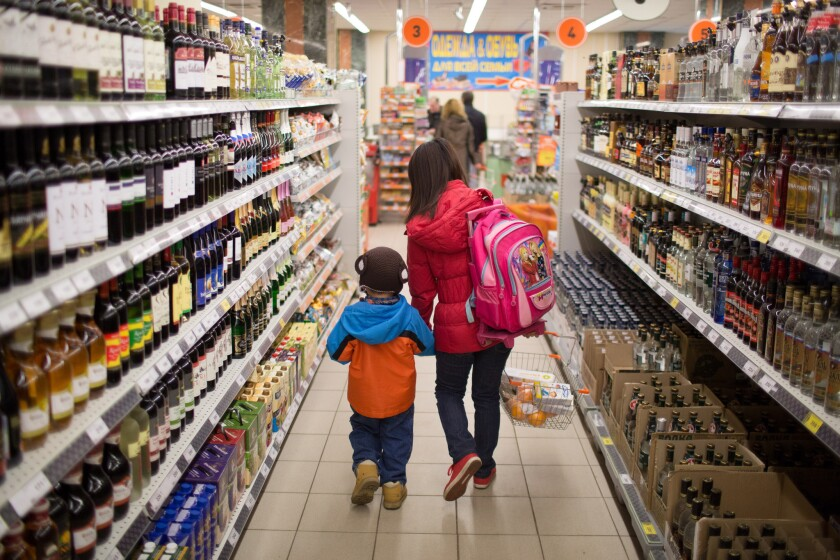 A customer and a child walk along the alcohol aisle inside a Dixy supermarket operated in Moscow, in a file photo from April.