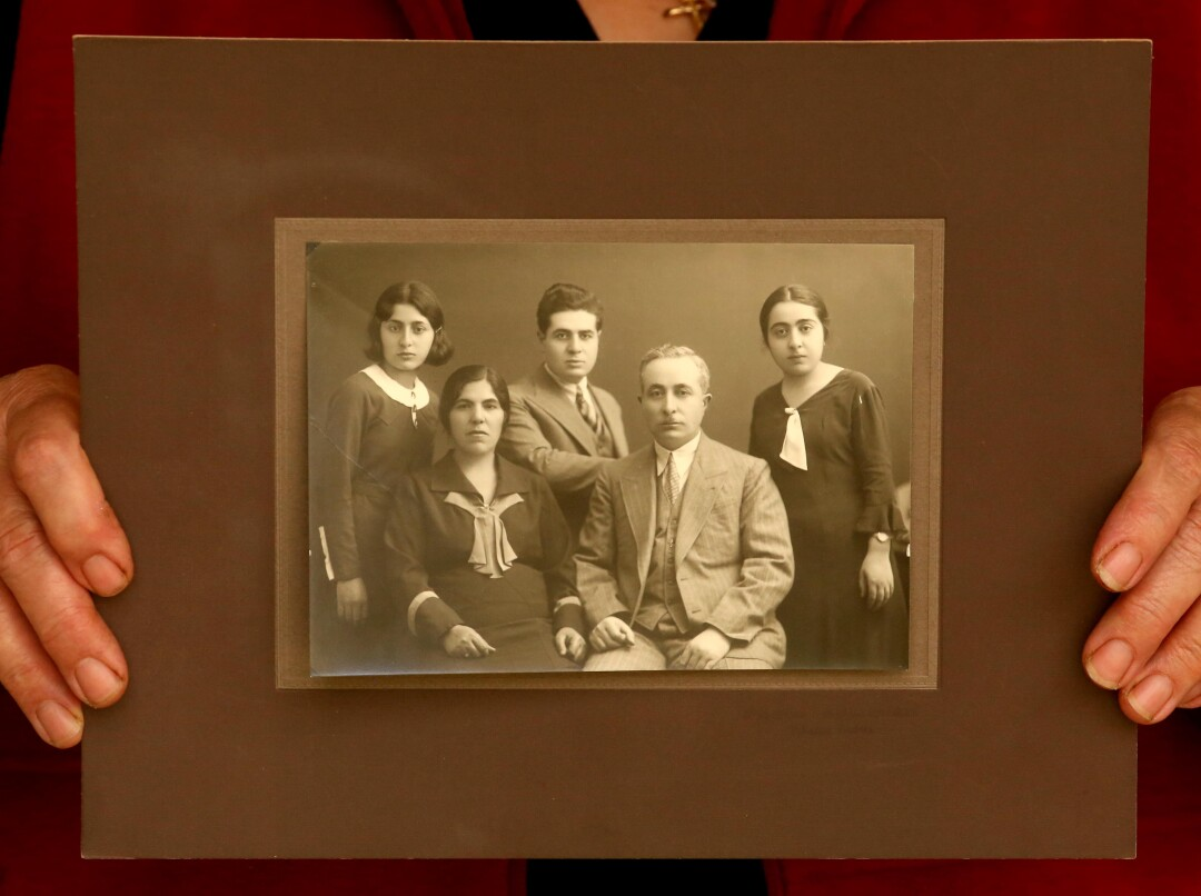 A family sits in an old, sepia-toned family portrait