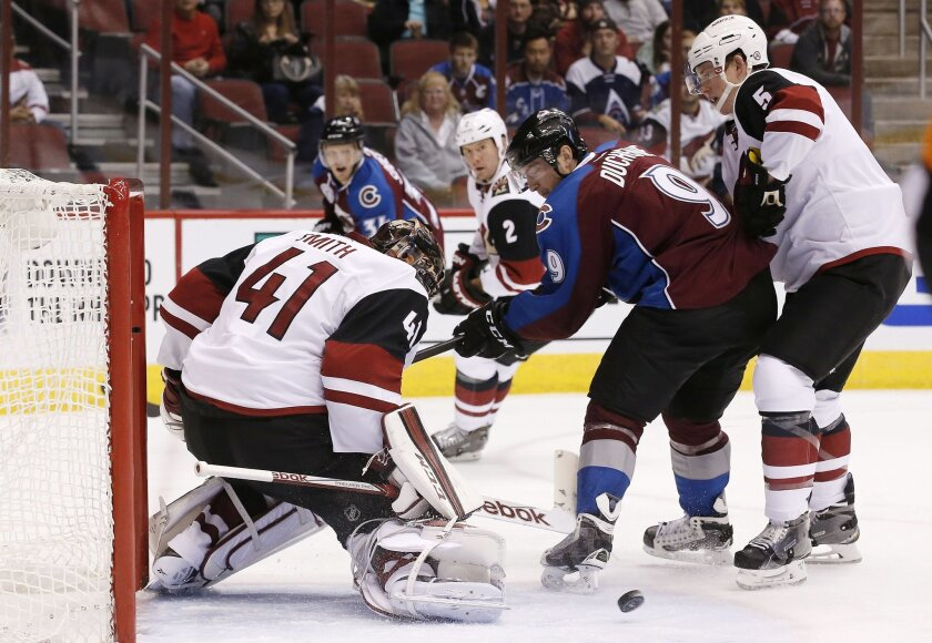 Arizona Coyotes' Mike Smith (41) makes a kick-save on a shot by Colorado Avalanche's Matt Duchene (9) as Coyotes' Connor Murphy (5) and Nicklas Grossmann (2), of Sweden, defend during the first period of an NHL hockey game Thursday, Nov. 5, 2015, in Glendale, Ariz. (AP Photo/Ross D. Franklin)