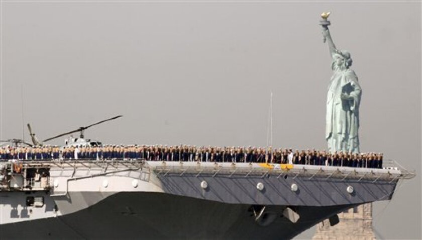 Marines and sailors line the deck of the U.S. Navy amphibious assault ship USS Iwo Jima as it passes the Statue of Liberty in New York on Wednesday, May 26, 2010.
