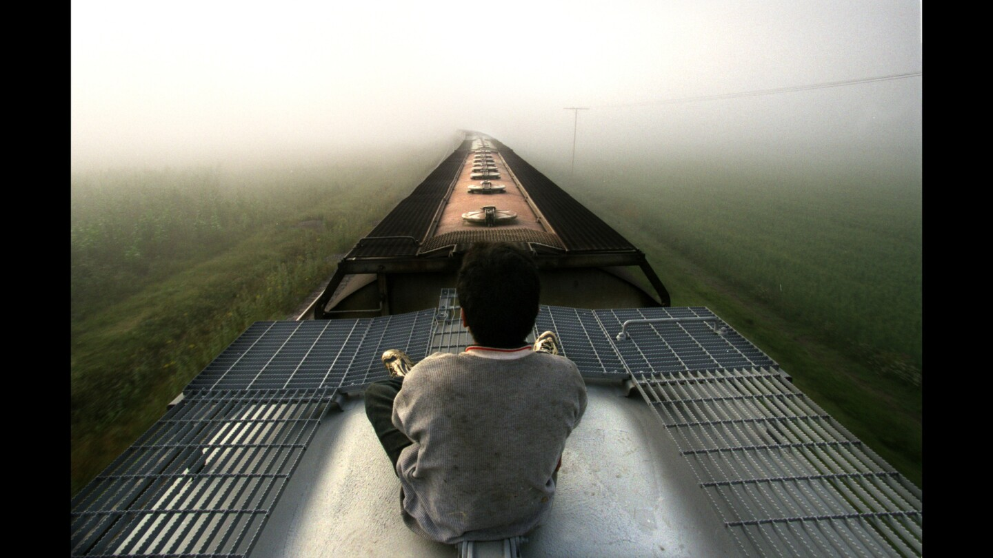 A Central American youth rides a freight train through Mexico toward the United States. Each year, thousands of children cling to the tops and sides of trains as they journey north in search of a parent. Some say they need to find out whether their mothers still love them.