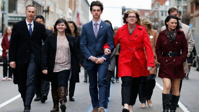 The family of Martin Richard, from left, Bill, Jane, Henry and Denise, walk down Boylston Street fol