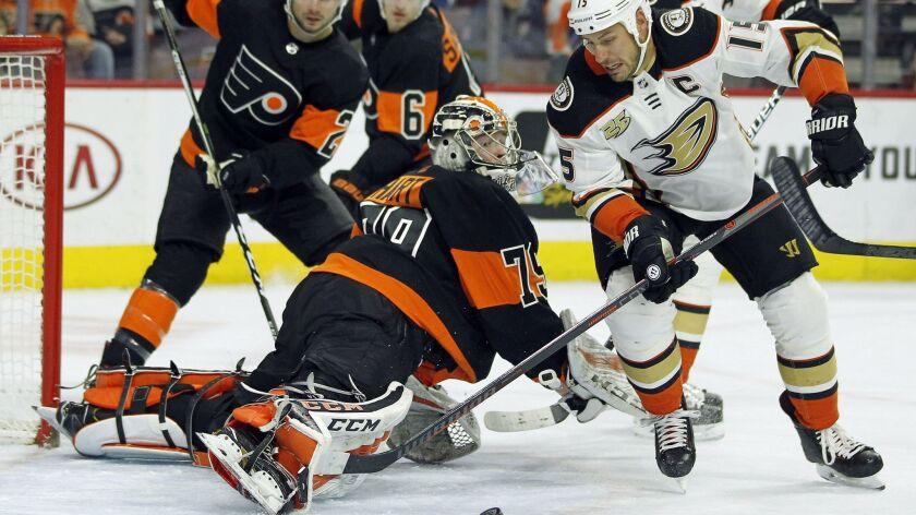 Philadelphia Flyers goalie Carter Hart sticks his leg out to block a scoring attempt by Anaheim Duck