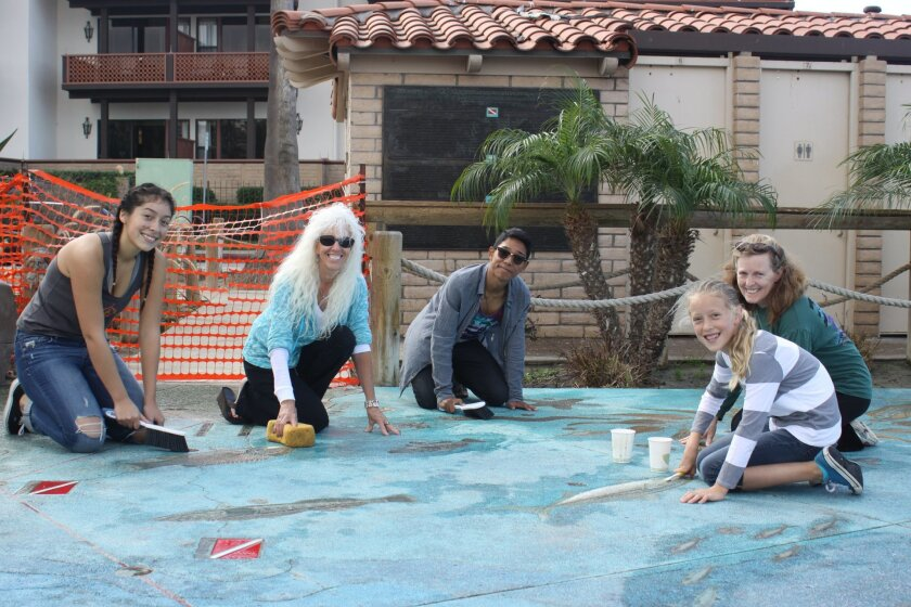 Volunteers Jade Appel, Terry Kraszewski, Sam Farber and Liora and Heidi Krantz, help clean the bronze fish imbedded in The Map educational installation and document their condition.