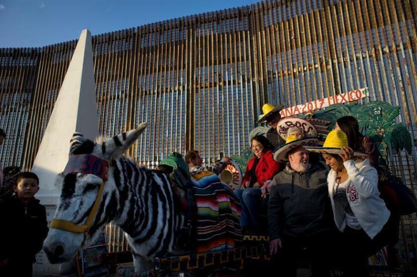 """El padre Pat Murphy (2d) director del refugio Casa del Migrante posa para una fotografía junto a la valla fronteriza entre los Estados Unidos y México el sábado 16 diciembre de 2017, durante la tradicional """"Posada Sin Fronteras"""" en Tijuana, México. EFE/Archivo"""