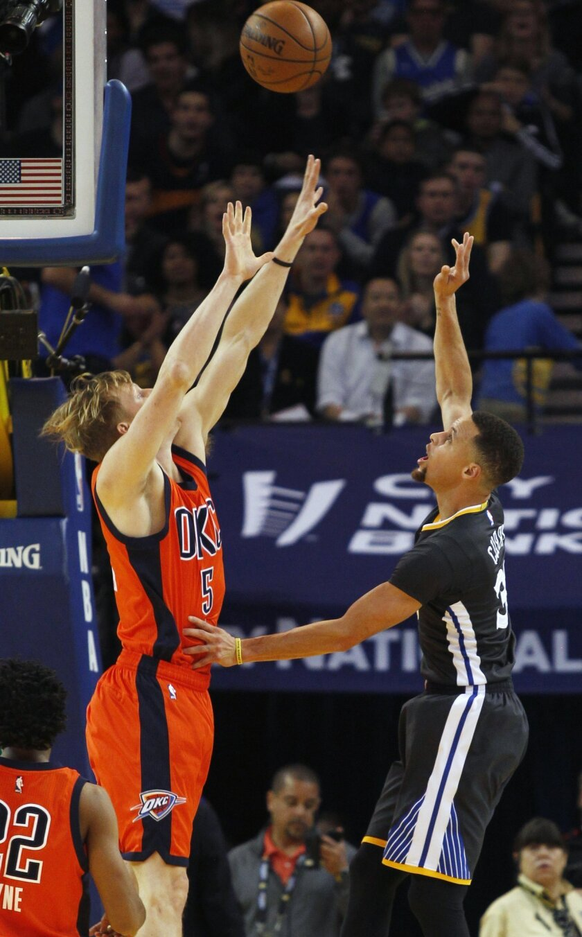 Golden State Warriors' Stephen Curry shoots over Oklahoma City Thunder's Kyle Singler during the first half of an NBA basketball game, Saturday, Feb. 6, 2016, in Oakland, Calif. (AP Photo/George Nikitin)